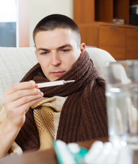 Sick ordinary man looking by thermometer