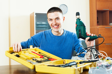 Handsome smiling man with toolbox holding drill