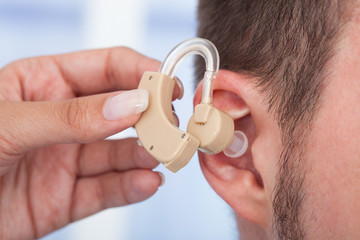 Doctor Inserting Hearing Aid In Man's Ear