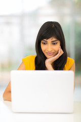indian woman looking at computer screen