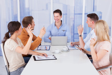 Colleagues Asking Question To Manager In Meeting