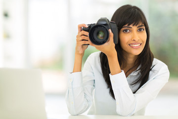 indian photographer holding a dslr camera