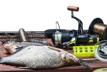fishing tackle and caught fish on the table isolated