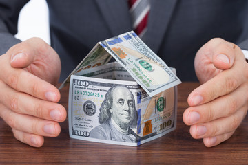 Businessman Sheltering House Made With Bank Notes