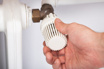 Man Adjusting Temperature On Radiator Thermostat