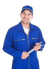 Mechanic In Blue Overalls Holding Spanner