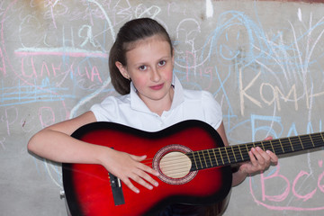 10-12 years girl playing a guitar