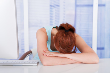 Tired Businesswoman Sleeping At Computer Desk