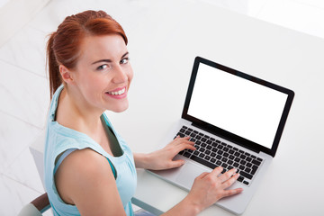 Beautiful Young Woman Using Laptop At Desk