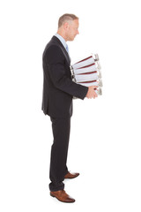 Sad Businessman Carrying Stack Of Binders