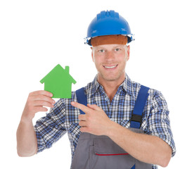 Confident Male Builder Holding Green House Model