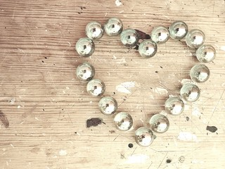 Glass pearl heart on wooden background