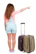 Back view of traveling pointing woman with suitcase