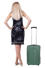 back view of standing young traveling blonde woman with suitcas