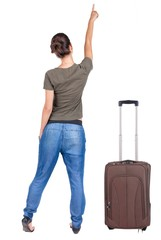 Back view of traveling pointing woman with suitcase.
