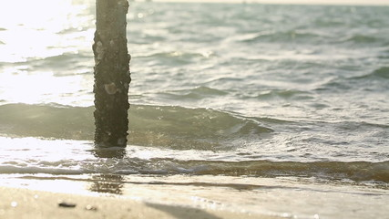 Waves breaking against the shoreline and a pier pillar