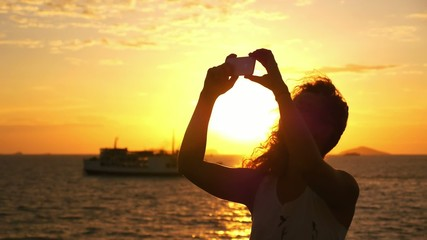 Beautiful Woman Taking Selfie against Sunset during Sea Cruise.