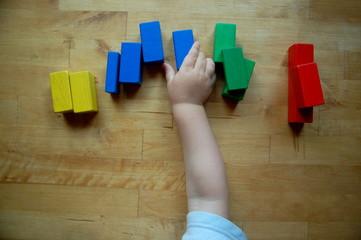 Kind sortiert Bausteine nach Farben