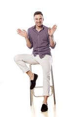happy handsome gay sitting on a bar stool and waving hands