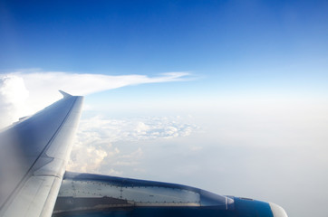 wing of plane with blue sky and white clouds .