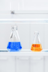 flasks with colorful liquids on a shelf in a chemical laboratory