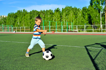 Boy playing football on football pitch