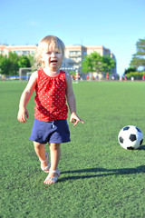 Young cheerful football fan girl on fresh green grass with ball