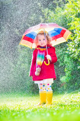 Little beauiful girl playing in the rain
