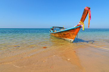 A long tail boat on a tropical island beach in thailand