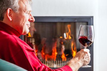 Mann trinkt Rotwein am Kamin