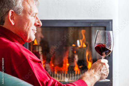 canvas print picture Mann trinkt Rotwein am Kamin