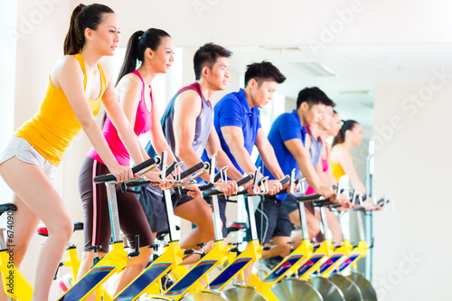 canvas print picture Asian people in spinning bike training at fitness gym