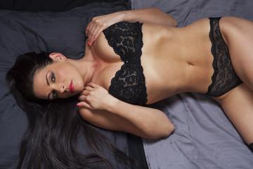 Frau in Unterwäsche im Bett liegend