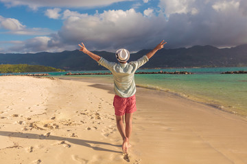 man walking on the beach and celebrates his joyous life