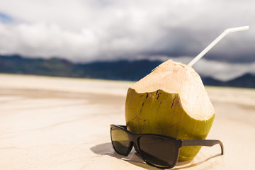sunglasses near coco nut with a straw on the beach