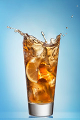 Glass of splashing iced tea with lemon