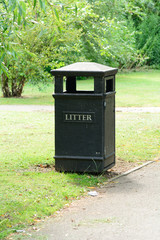 Black litter bin in park