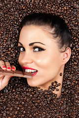 attractive woman in a coffee beans with chocolate in hand