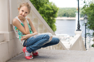 Cute young girl sitting on an outdoor staircase