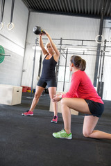 Woman lift kettlebells with personal trainer
