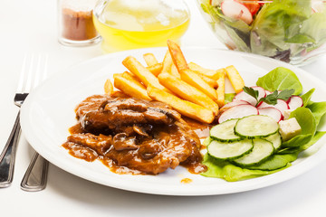 Pork chop with sauce, mushrooms and chips