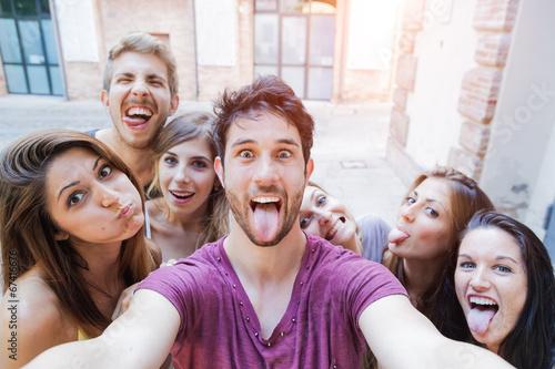 Leinwanddruck Bild Selfie adolescenti si scattano foto in città