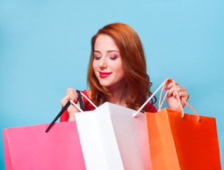 Redhead girl with shopping bags on blue background.