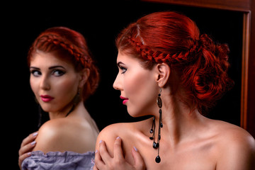 Young elegant woman looking in the mirror