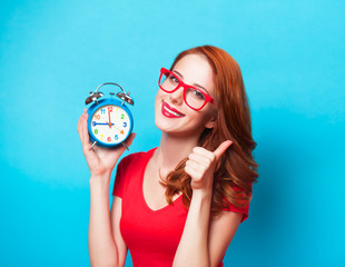 Redhead girl with alarm clock on blue background.