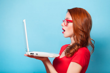 Redhead girl with laptop on blue background.
