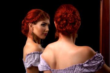 Elegant woman looking in the mirror