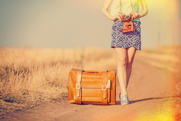 girl with suitcase on country road.