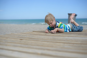 Boy resting on a wooden walkway on the beach