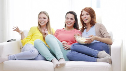 three smiling teenage girls watching tv at home